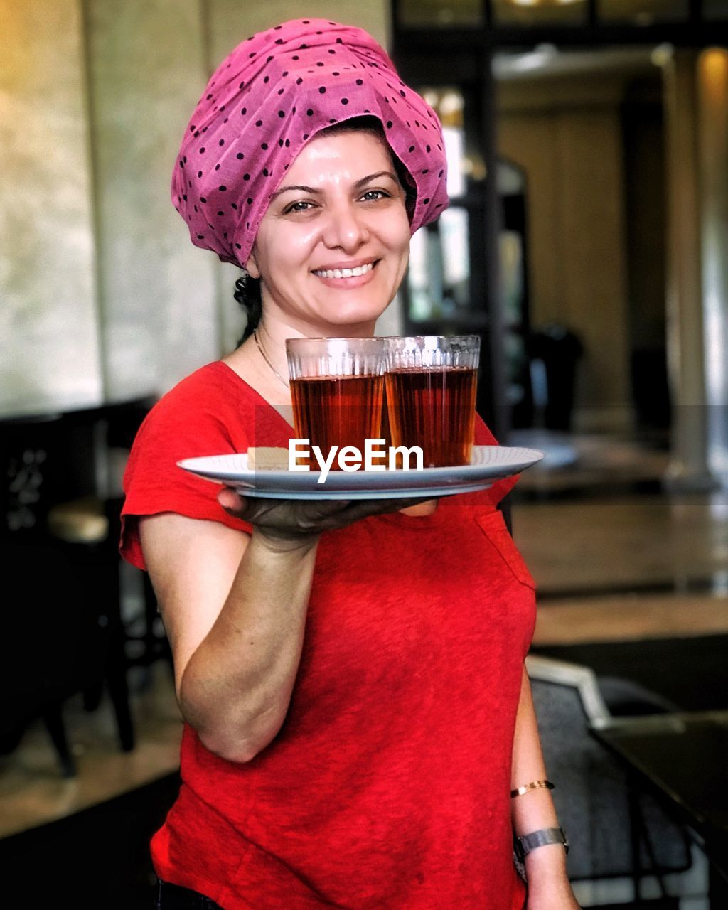 food and drink, portrait, one person, front view, looking at camera, smiling, drink, happiness, refreshment, young adult, holding, focus on foreground, indoors, real people, women, adult, lifestyles, emotion, leisure activity, cup, hot drink