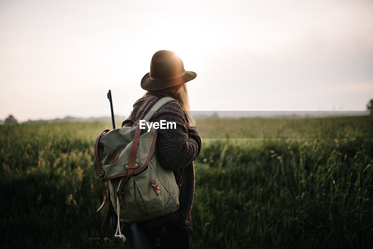 field, land, real people, sky, plant, rear view, women, adult, standing, hat, nature, three quarter length, lifestyles, leisure activity, grass, environment, landscape, people, casual clothing, growth, positive emotion, outdoors