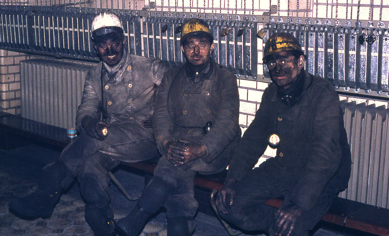 Portrait Of Firefighters Sitting On Bench Against Wall