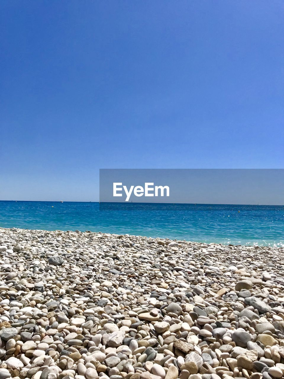 sea, water, sky, horizon over water, horizon, beach, beauty in nature, rock, solid, land, tranquility, tranquil scene, copy space, nature, scenics - nature, blue, clear sky, pebble, day, stone - object, no people, outdoors