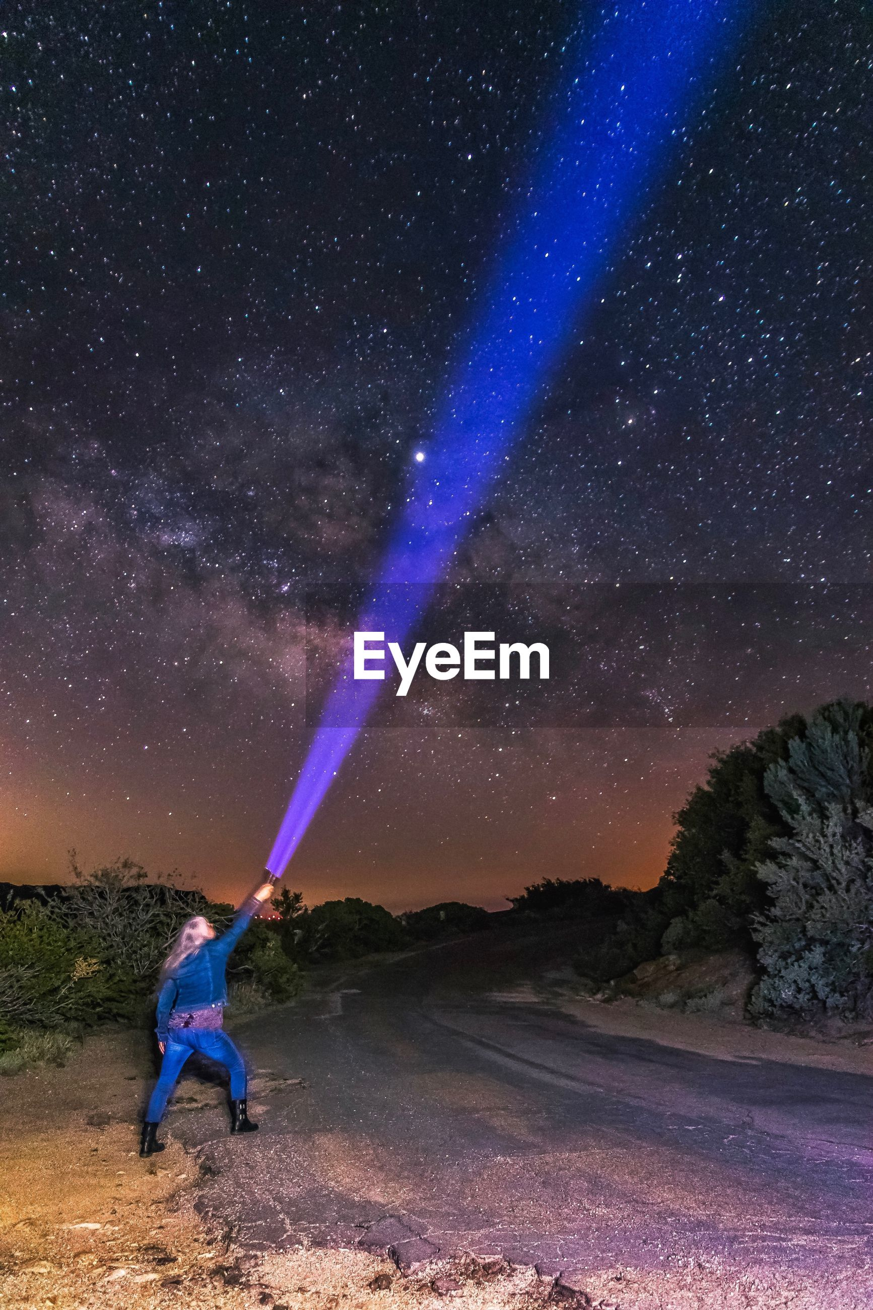 Woman holding flashlight towards star field in field against sky at night