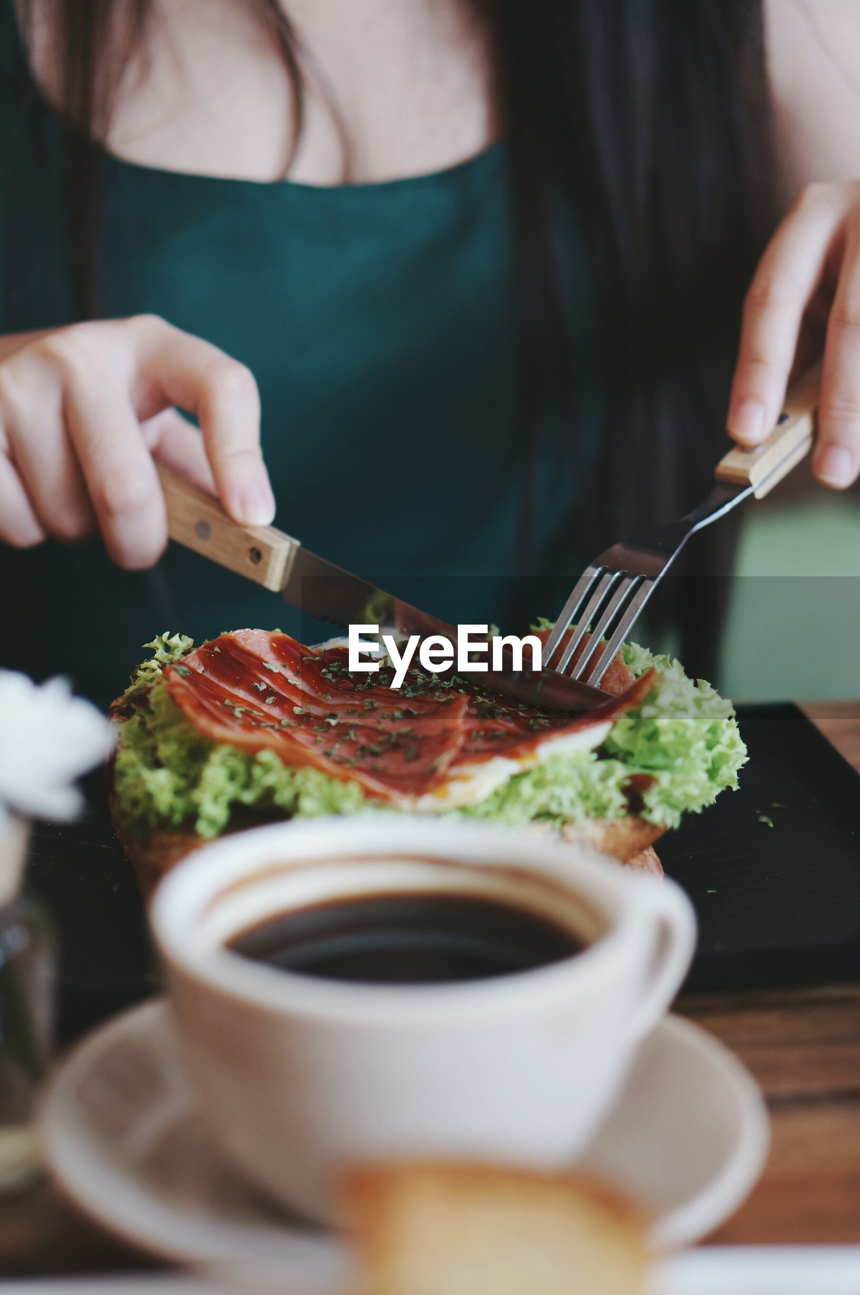 Midsection of woman using cutlery while cutting food