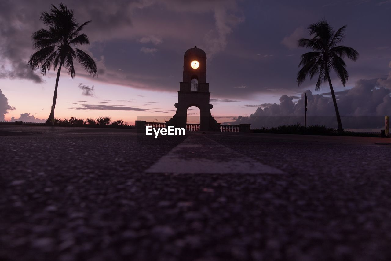 sky, tree, palm tree, plant, surface level, sunset, cloud - sky, nature, tropical climate, architecture, silhouette, dusk, transportation, no people, street, direction, built structure, asphalt, diminishing perspective, city, outdoors