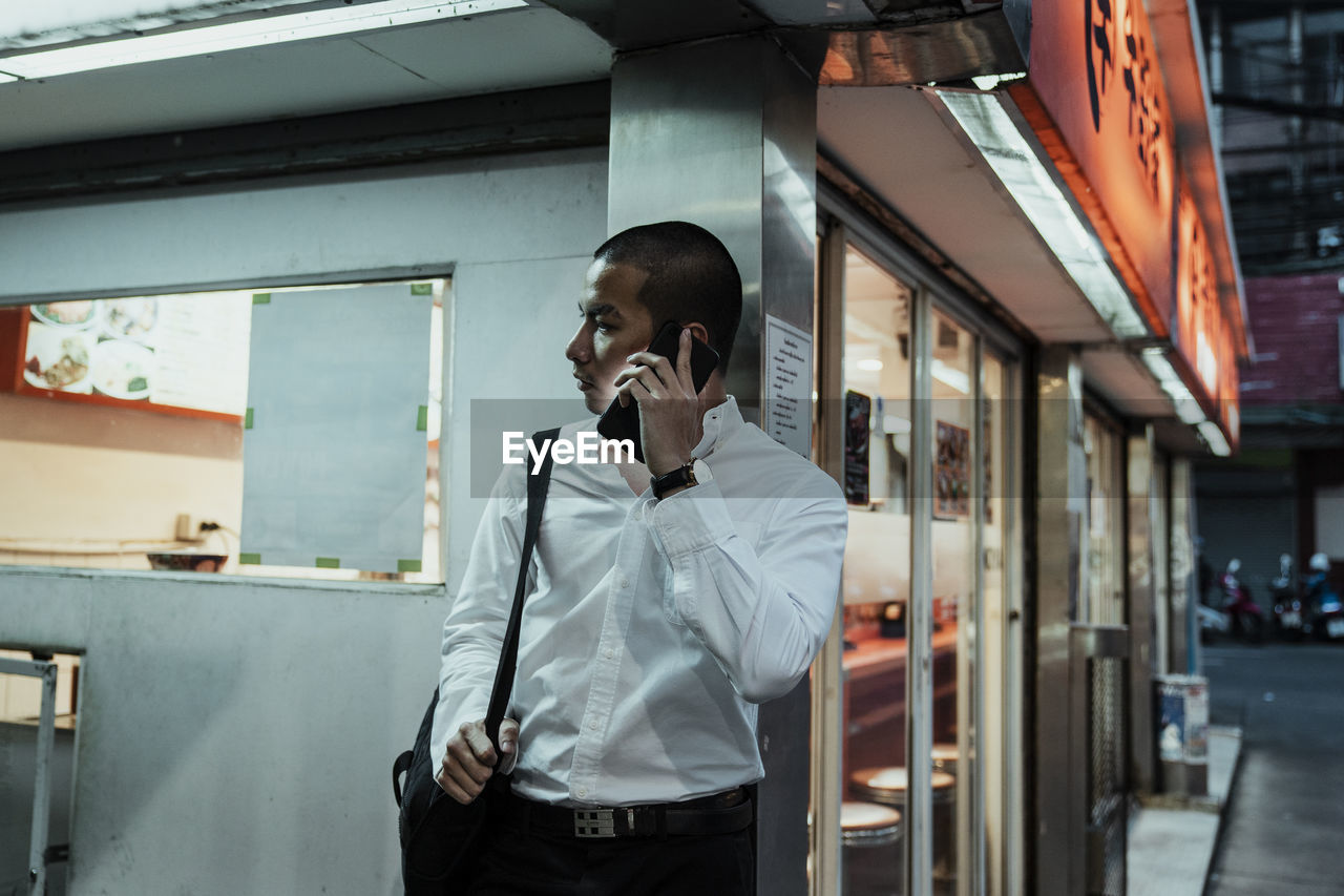 Businessman talking over smart phone while standing against wall