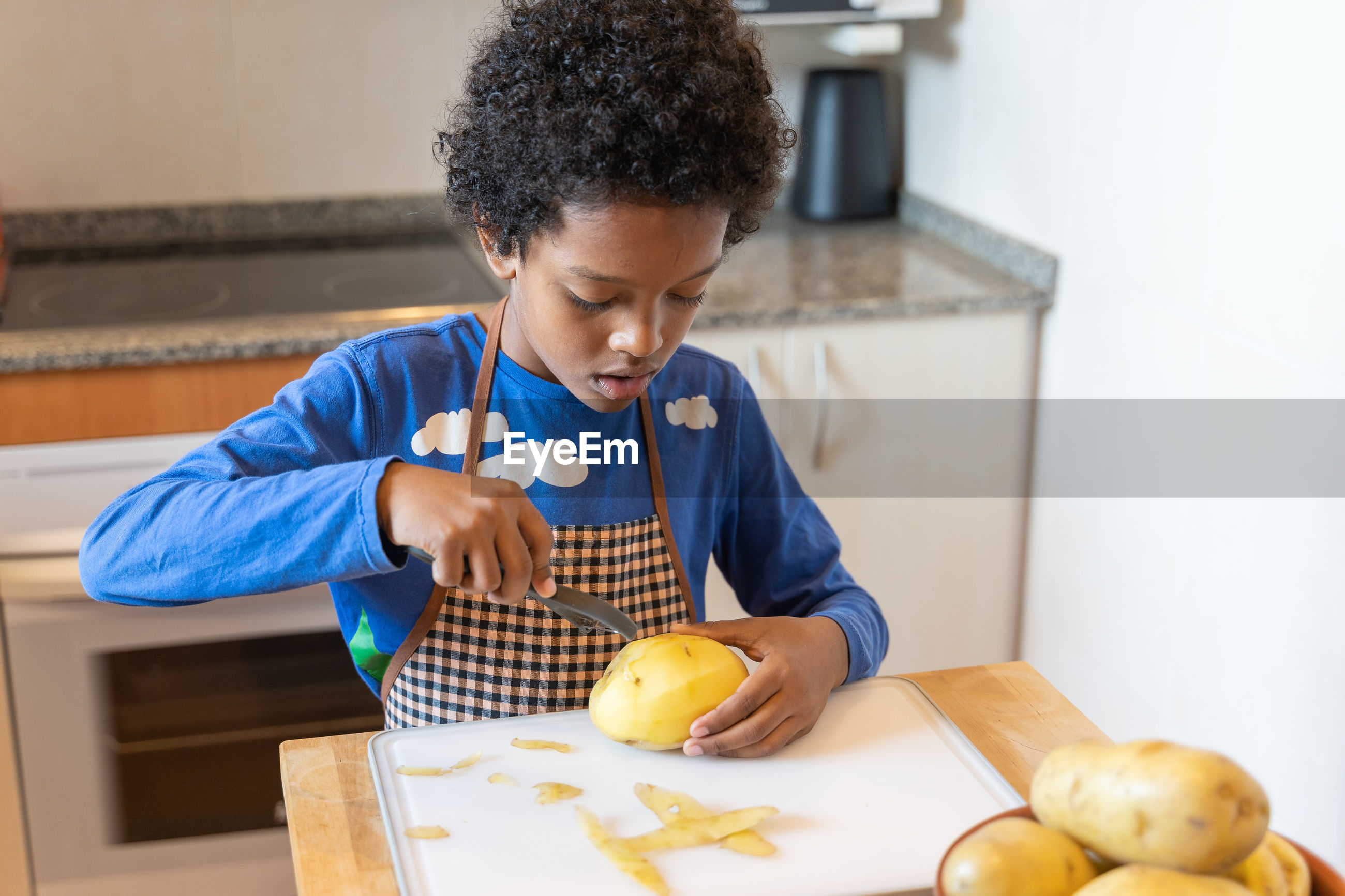 Boy peeling raw potato at home