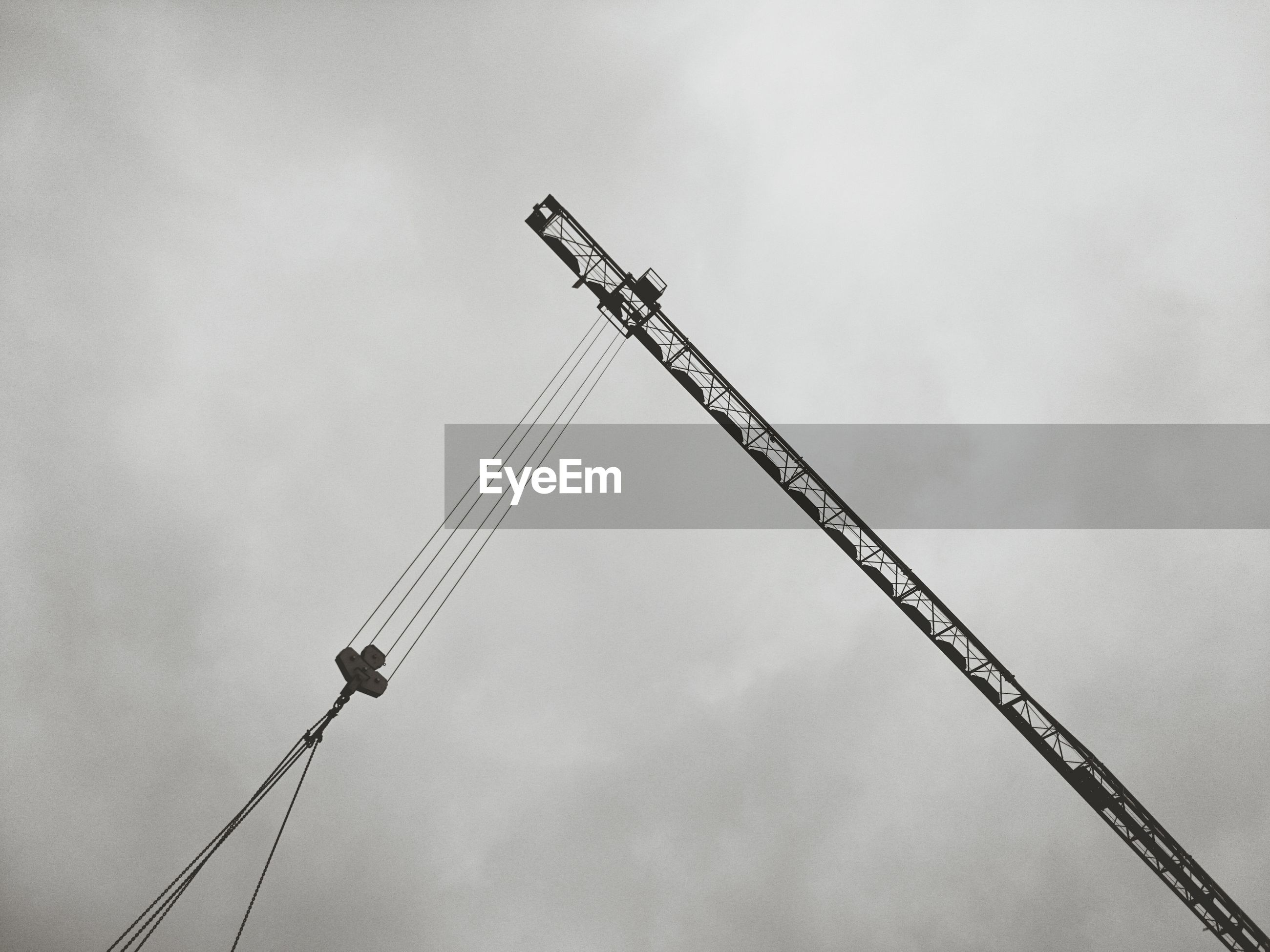 Low angle view of crane at construction site against sky at dusk