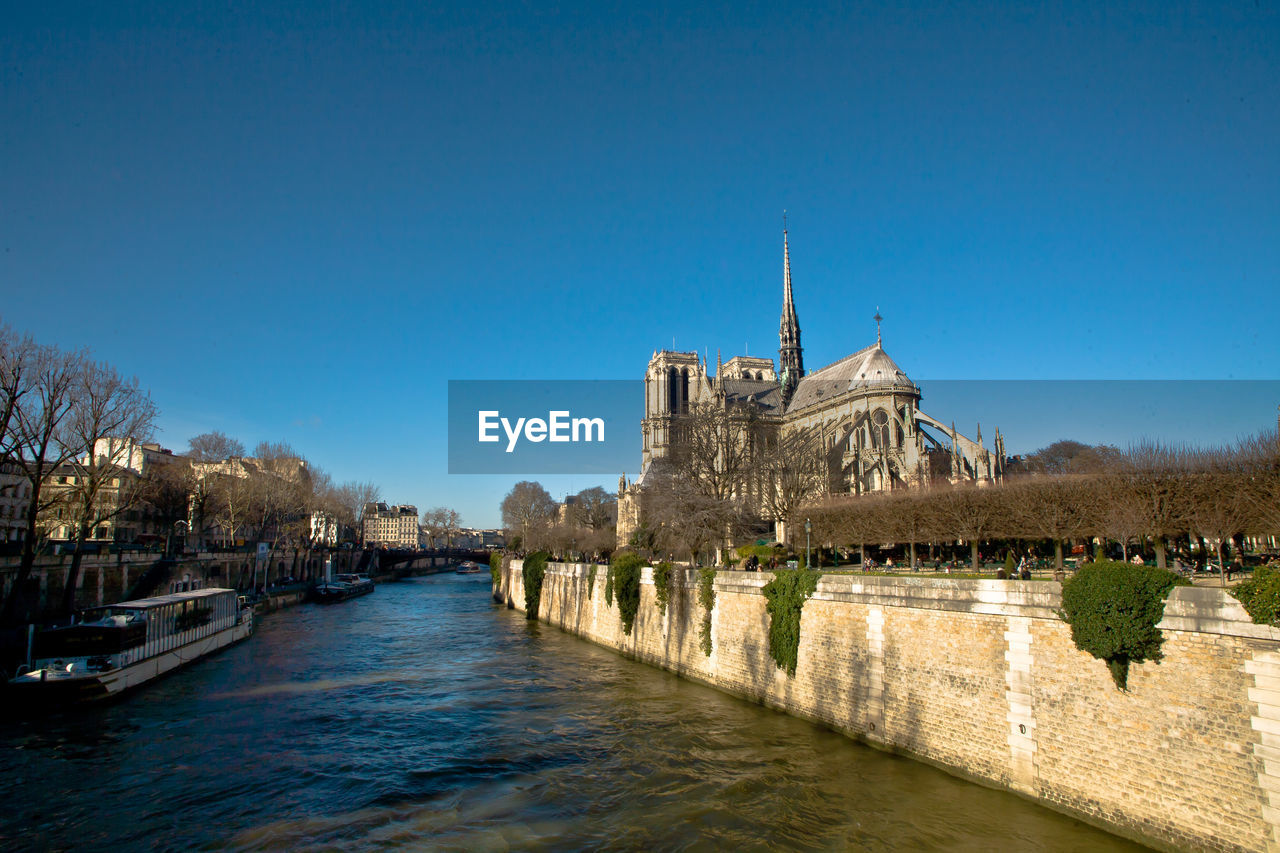 architecture, built structure, water, history, river, building exterior, travel destinations, tourism, outdoors, place of worship, bridge - man made structure, clear sky, religion, spirituality, blue, no people, day, sky, city, tree