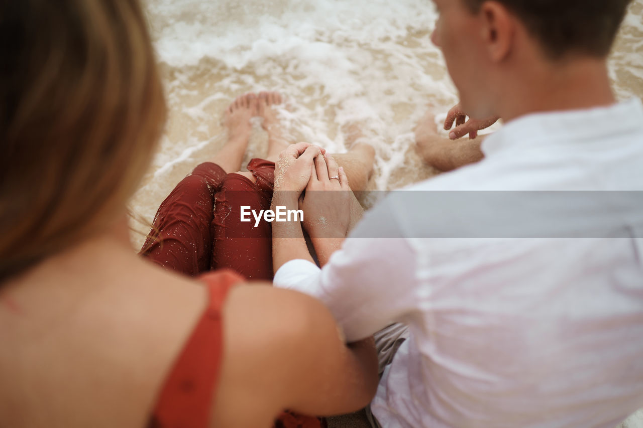 High angle view of young couple sitting at shore