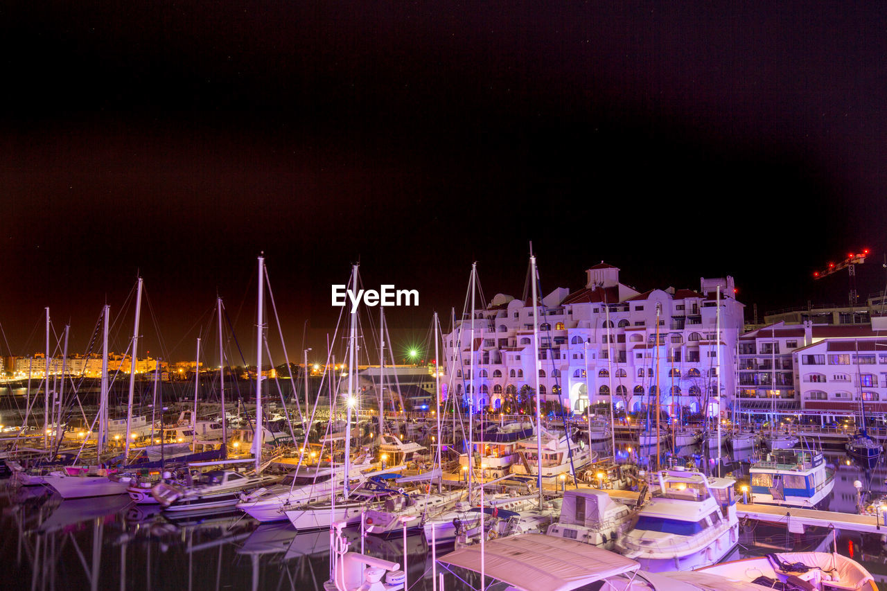 Boats Moored At Harbor During Night