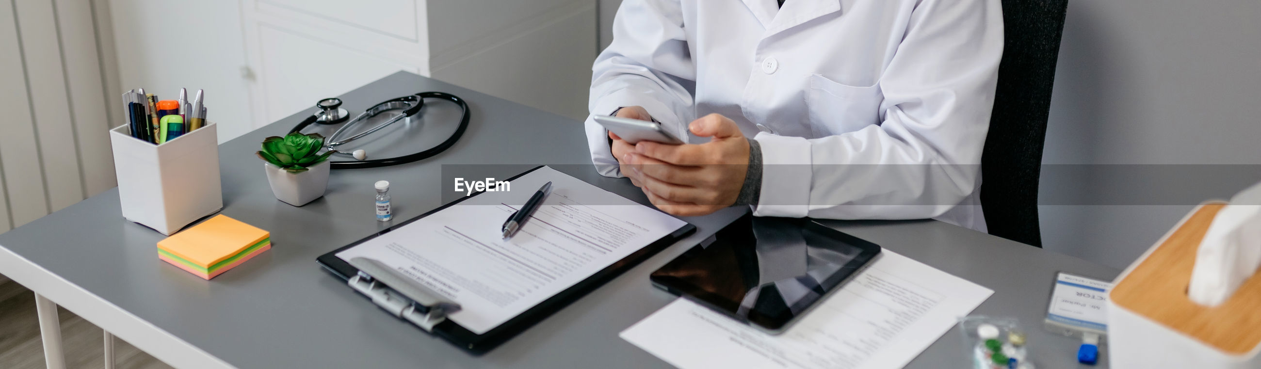 Midsection of doctor using mobile phone at desk