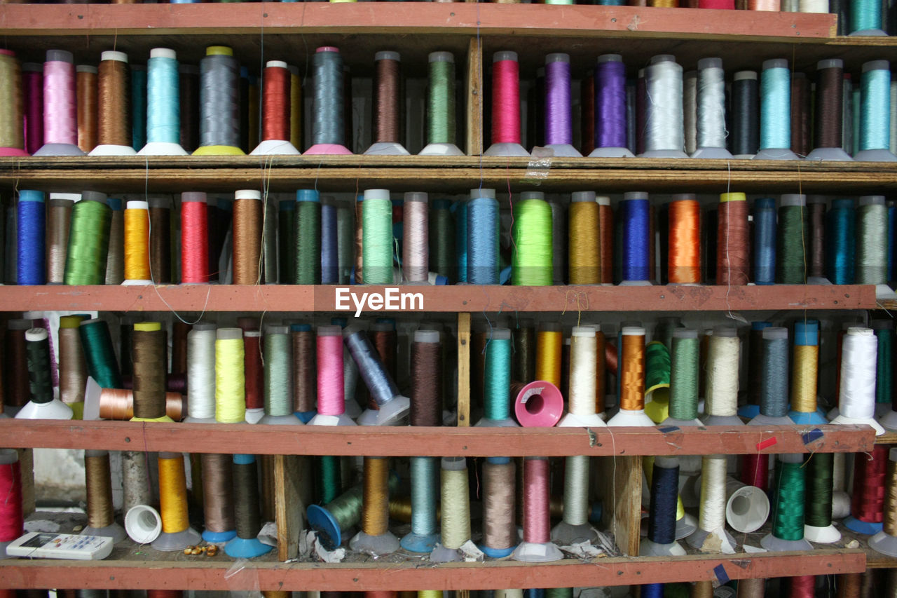 multi colored, large group of objects, choice, shelf, variation, indoors, arrangement, no people, still life, abundance, order, full frame, side by side, in a row, close-up, thread, spool, collection, backgrounds, textile