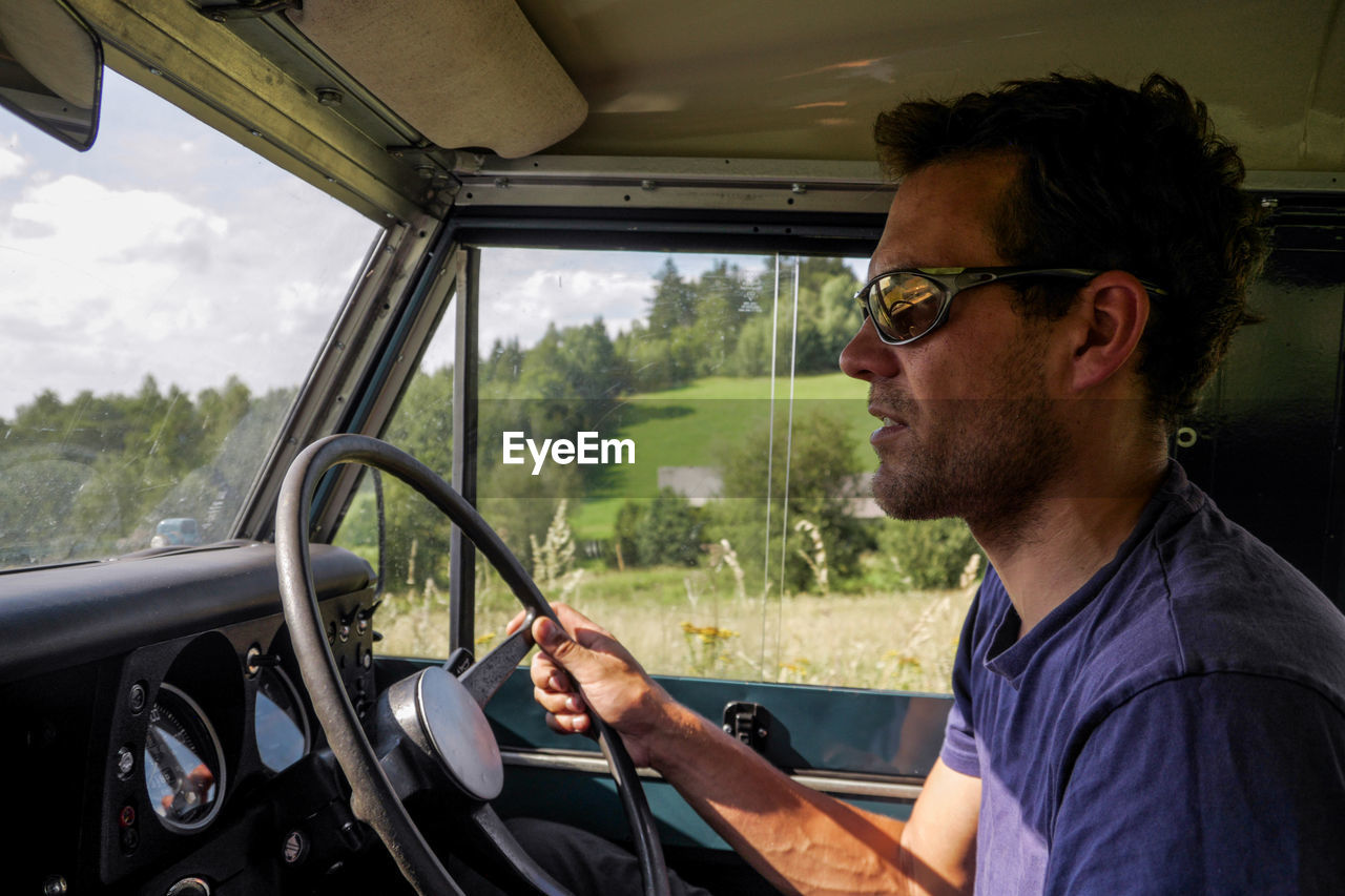 Profile view of man driving vehicle