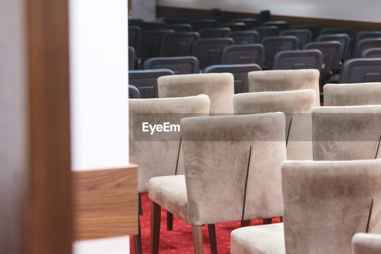 seat, chair, in a row, indoors, empty, no people, absence, large group of objects, focus on foreground, repetition, arrangement, selective focus, table, arts culture and entertainment, auditorium, side by side, movie theater, close-up, theater, order
