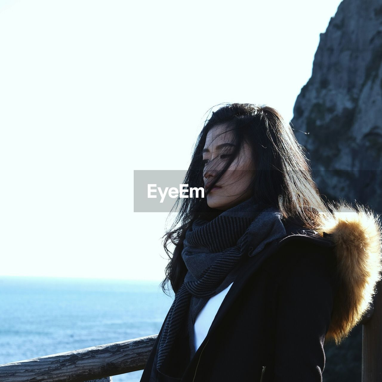 Young woman looking at sea against clear sky