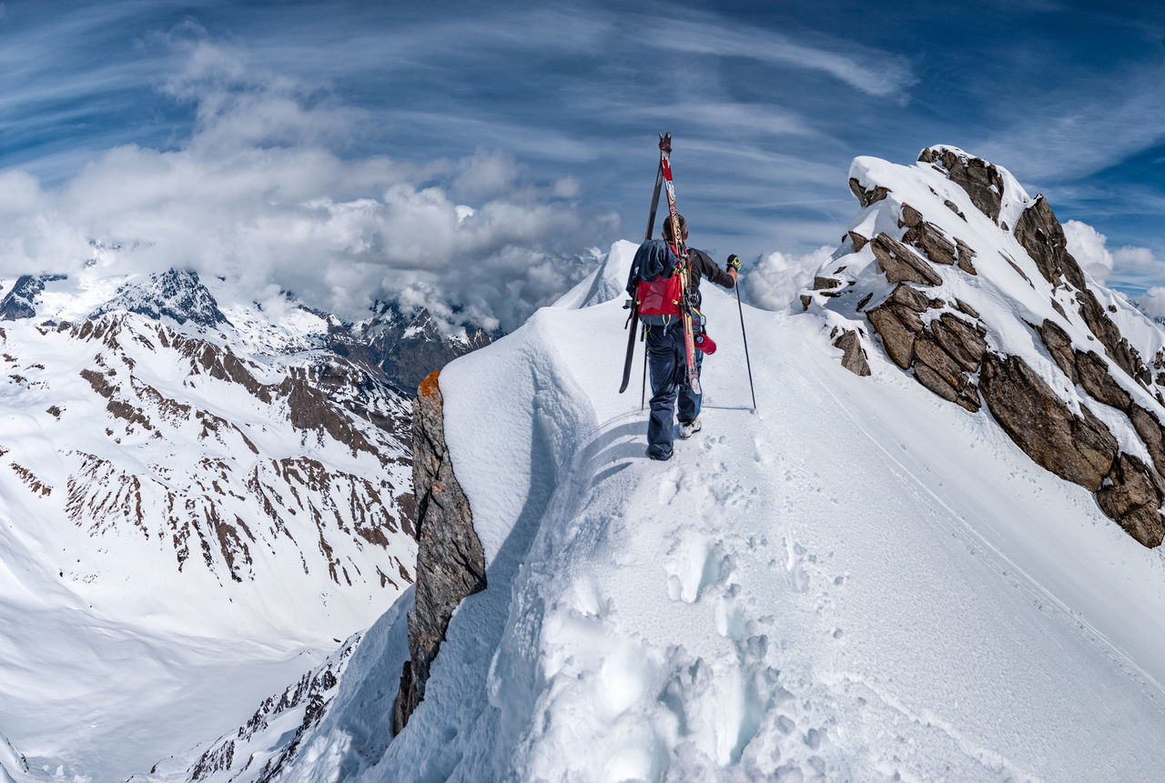 PANORAMIC VIEW OF PEOPLE ON SNOWCAPPED MOUNTAINS