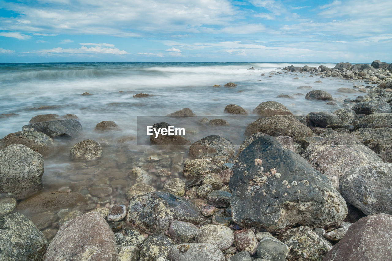 sea, sky, rock, water, solid, cloud - sky, beauty in nature, horizon over water, beach, horizon, rock - object, nature, scenics - nature, land, tranquility, tranquil scene, no people, stone, day, outdoors, pebble, shallow, rocky coastline
