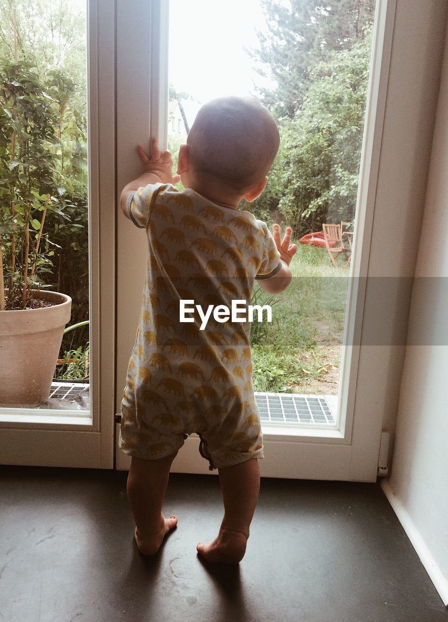 Rear view of baby boy standing against closed door at home