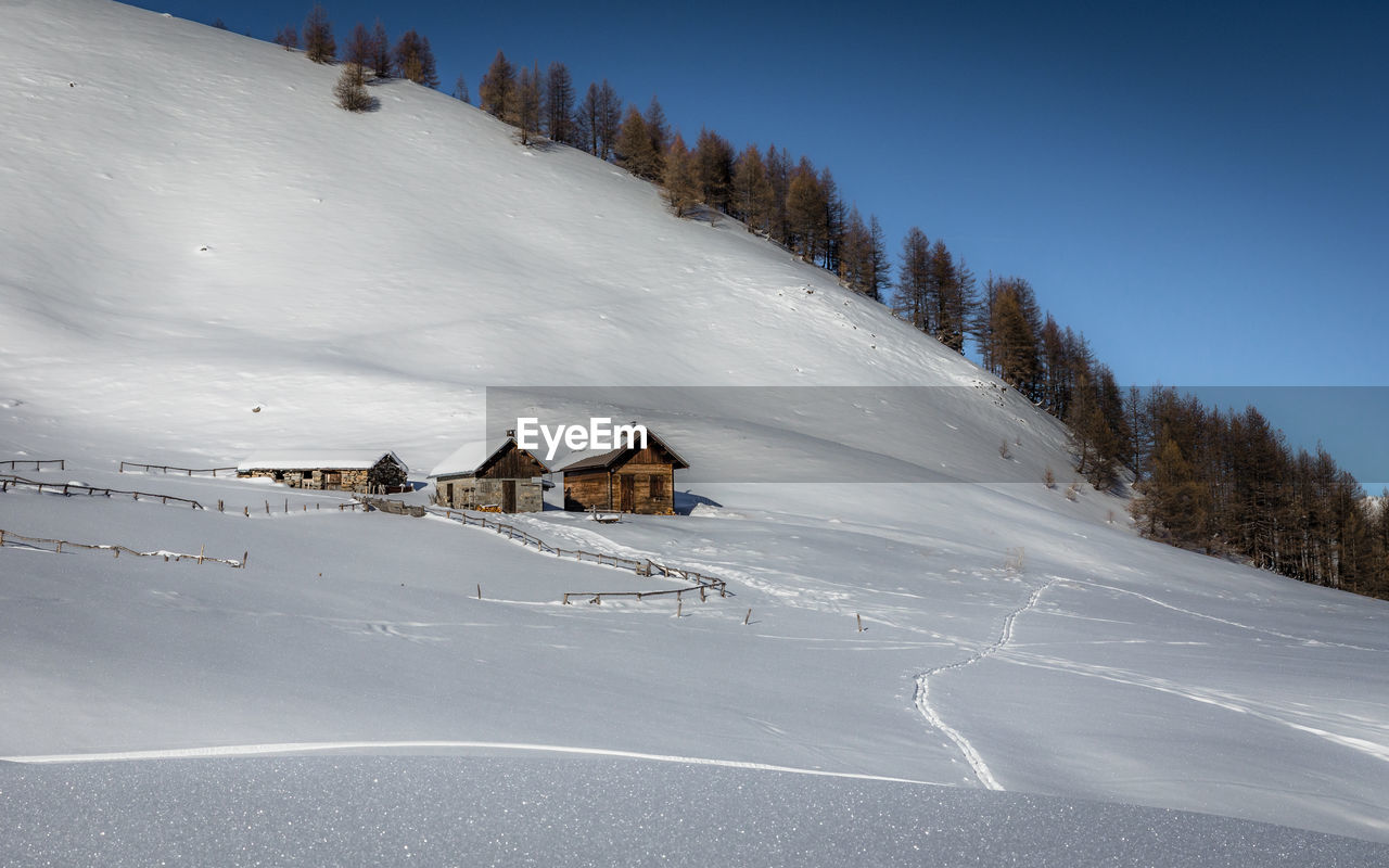 SNOW COVERED LANDSCAPE AND BUILDINGS AGAINST SKY