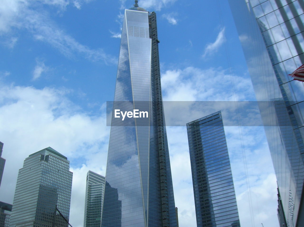 Low angle view of modern skyscrapers against cloudy sky