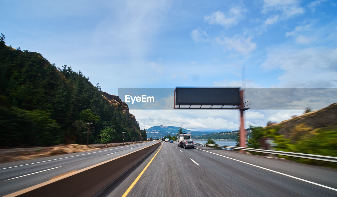 transportation, road, sky, direction, cloud - sky, sign, nature, mode of transportation, symbol, the way forward, marking, road marking, car, tree, land vehicle, mountain, day, motor vehicle, diminishing perspective, plant, no people, outdoors, dividing line