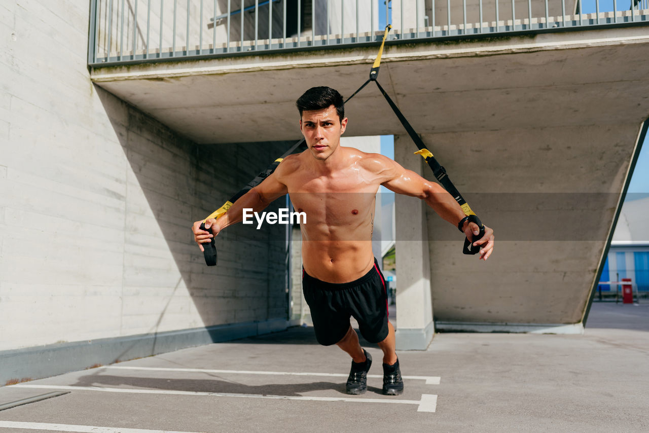 FULL LENGTH PORTRAIT OF SHIRTLESS YOUNG MAN STANDING AGAINST WALL