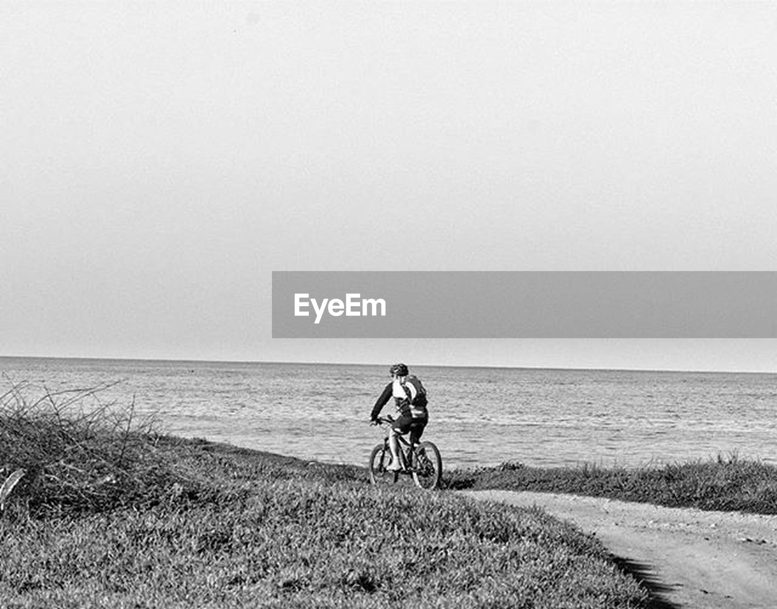 horizon over water, sea, clear sky, beach, copy space, water, shore, bicycle, tranquility, tranquil scene, sand, scenics, full length, nature, beauty in nature, men, leisure activity, sky