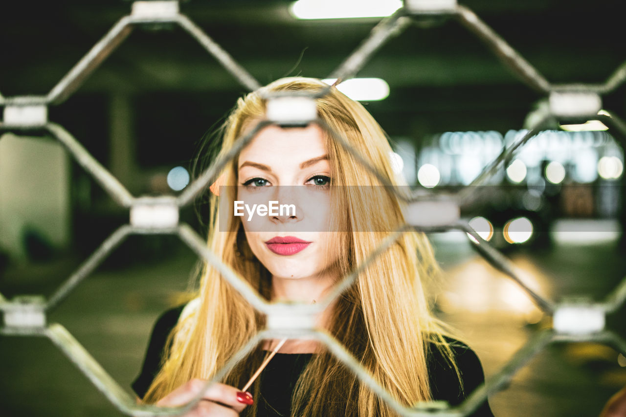 Portrait Of Beautiful Young Woman Seen Through Chainlink Fence In Basement