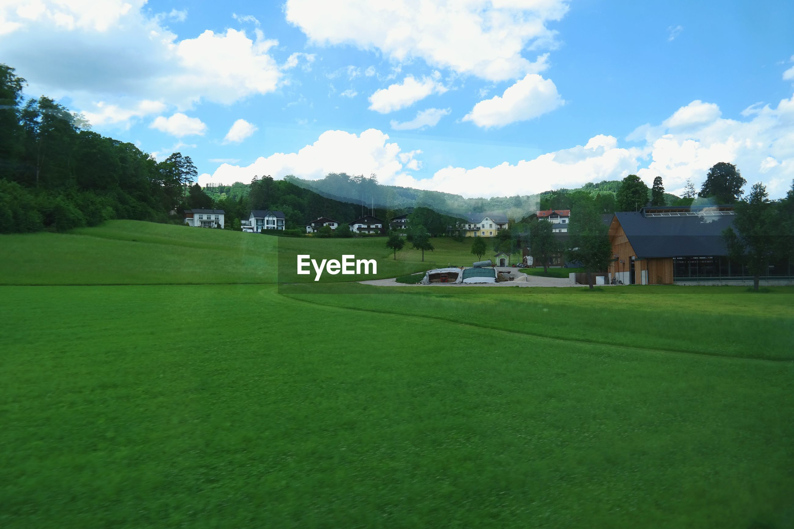 SCENIC VIEW OF GRASSY FIELD AGAINST HOUSES
