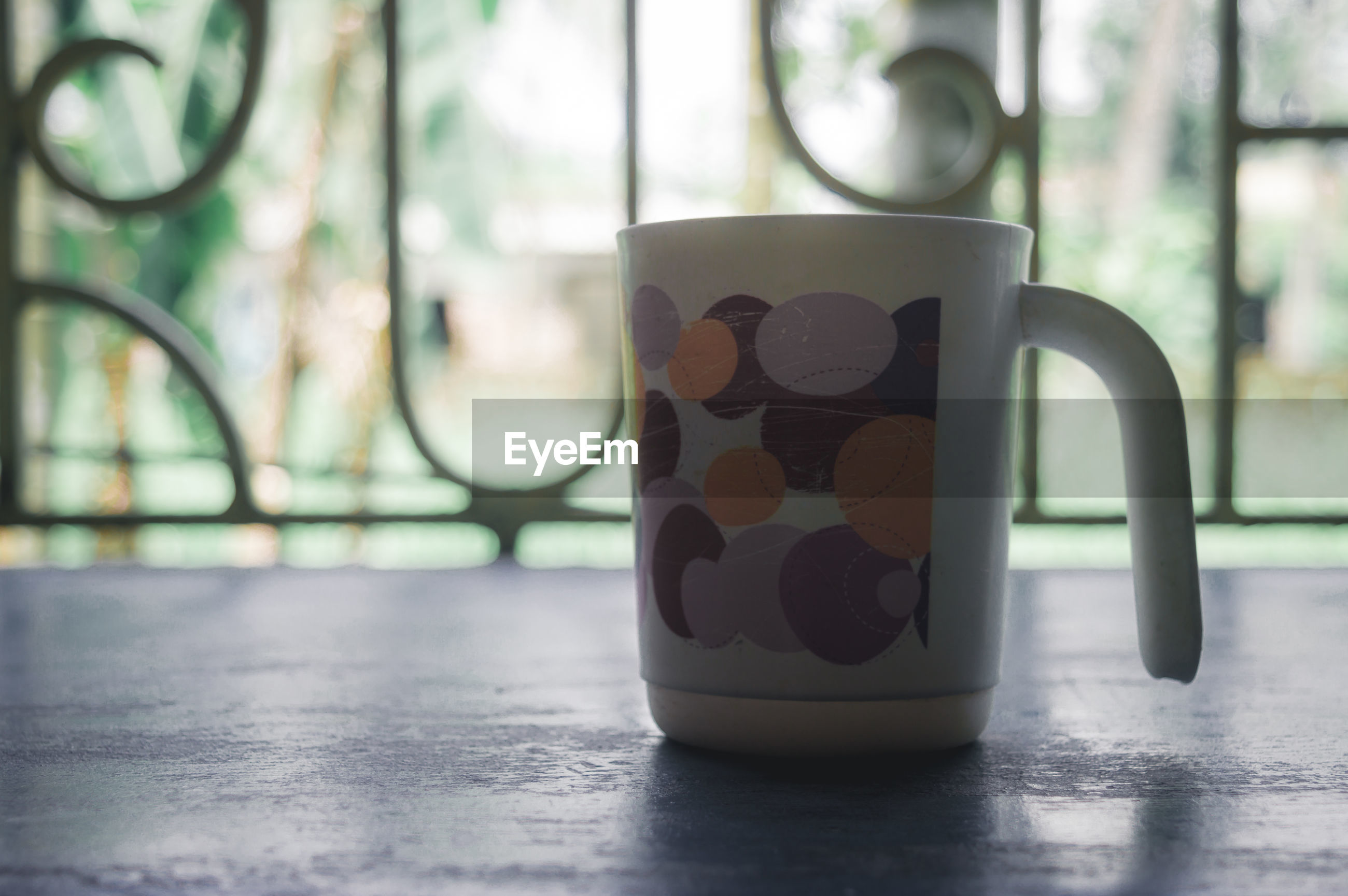 CLOSE-UP OF COFFEE CUP ON TABLE WITH REFLECTION