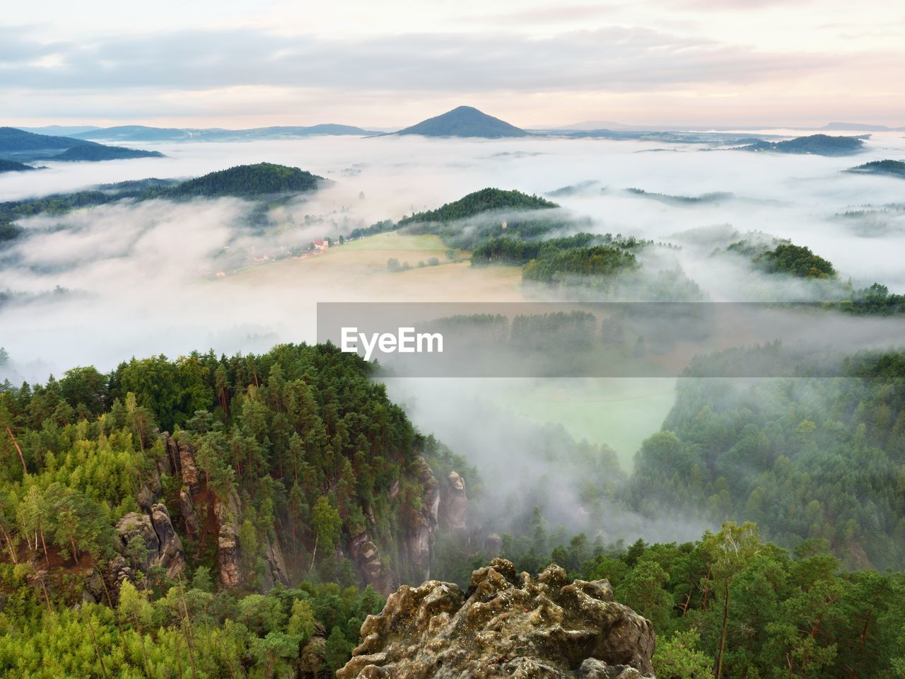 Spring misty landscape. morning in beautiful hills of natural park. rocky peaks in heavy creamy fog.