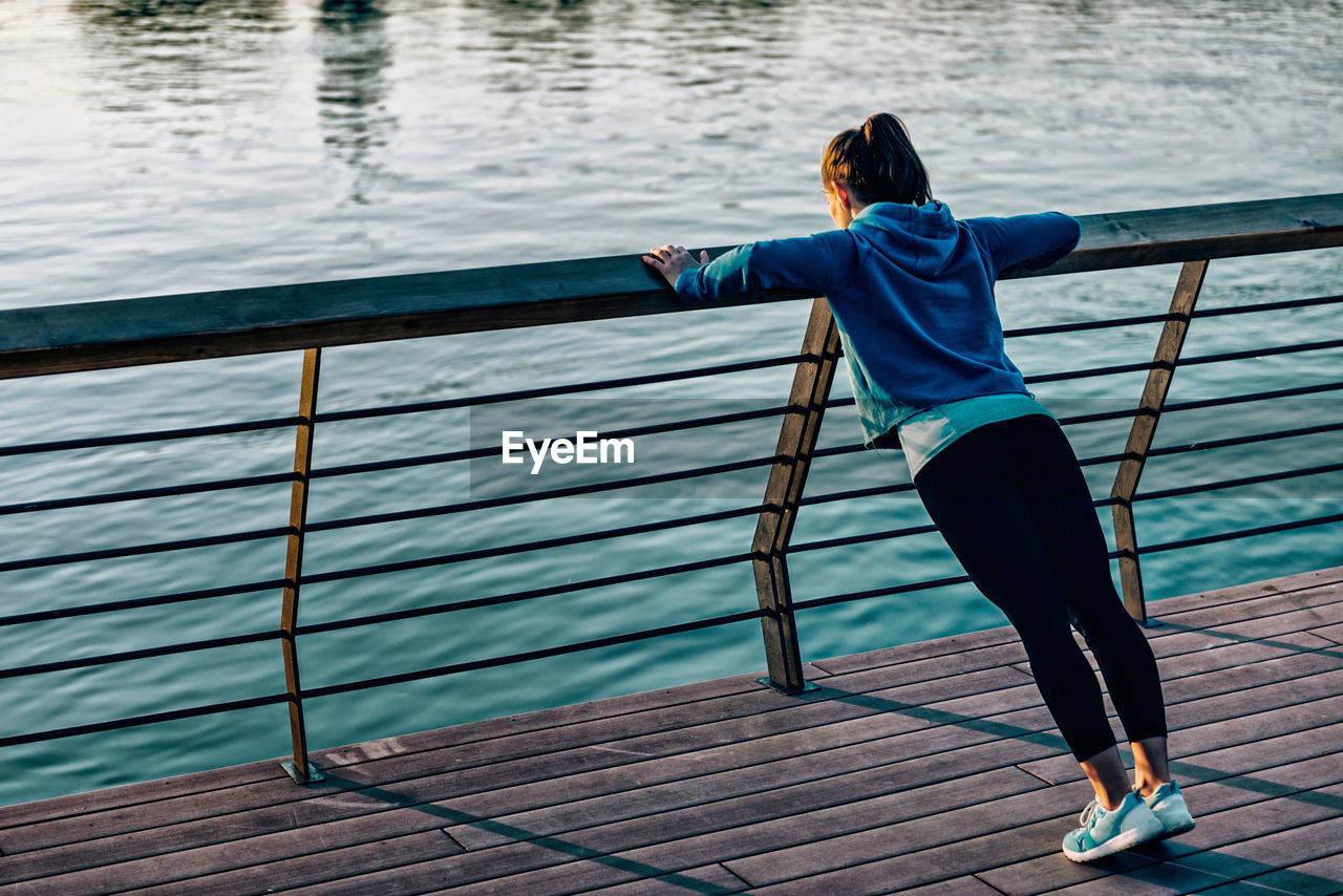 Young woman exercising on railing by river during sunset