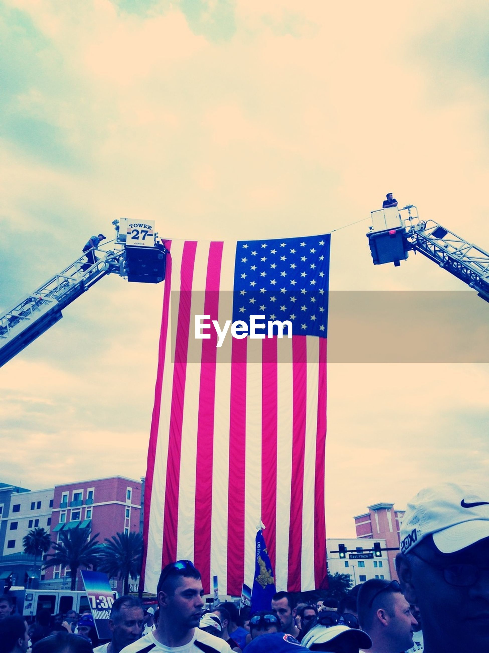 flag, sky, low angle view, national flag, patriotism, american flag, identity, cloud - sky, built structure, architecture, city, tall - high, building exterior, capital cities, cloud, tower, transportation, famous place, day, travel destinations