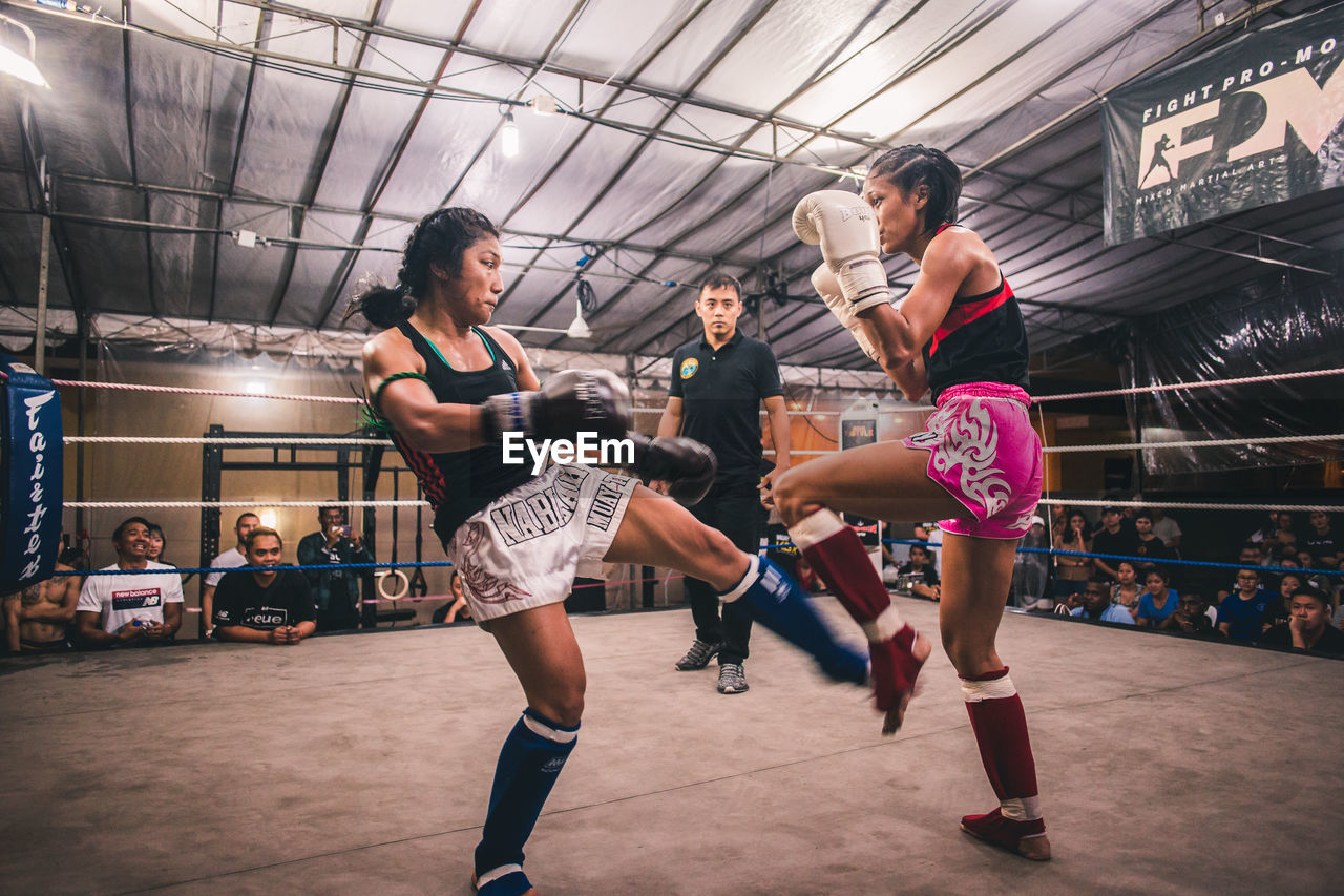 group of people, women, sport, real people, adult, lifestyles, indoors, motion, boxing - sport, people, vitality, leisure activity, full length, clothing, sports clothing, young women, young adult, strength, togetherness, ceiling, hairstyle, effort