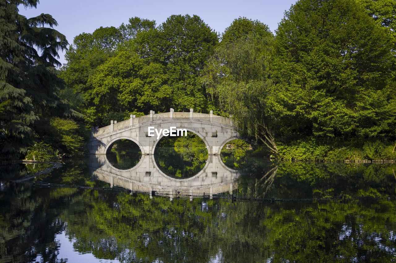 Arch Bridge Over Lake Against Trees