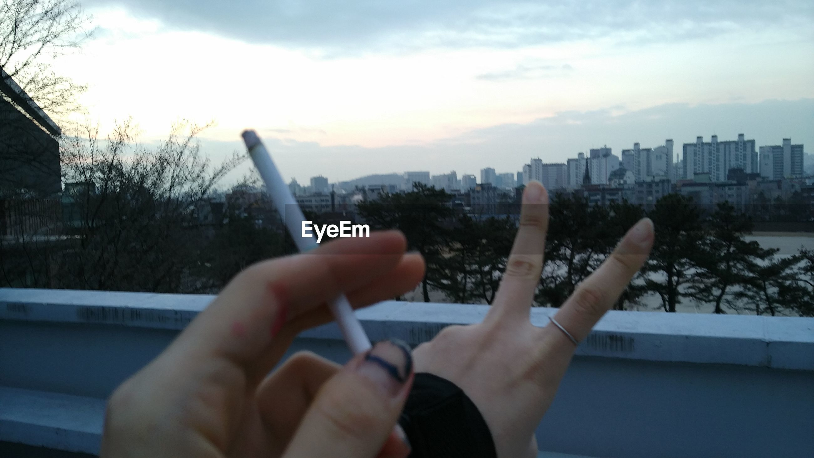 person, building exterior, personal perspective, architecture, sky, built structure, city, part of, holding, lifestyles, cropped, tree, human finger, leisure activity, cityscape, cloud, unrecognizable person