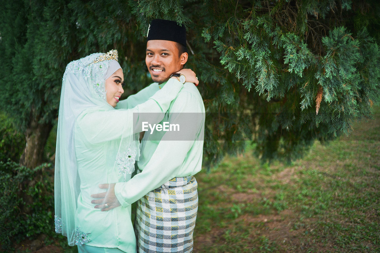 two people, emotion, togetherness, smiling, happiness, men, standing, real people, bonding, young adult, couple - relationship, males, love, young men, looking at camera, positive emotion, plant, young women, women, adult, outdoors