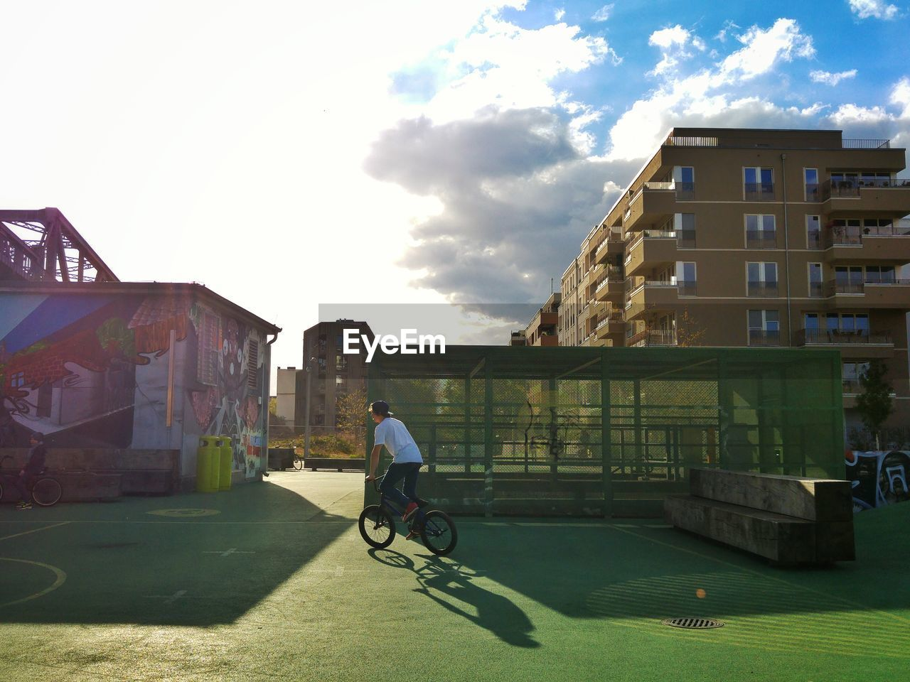 architecture, built structure, building exterior, sunlight, bicycle, day, outdoors, real people, full length, one person, sky, city, city life, men, leisure activity, lifestyles, shadow, standing, grass, people