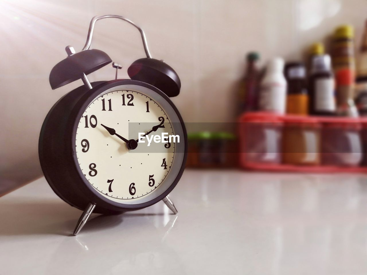 indoors, clock, focus on foreground, time, container, still life, table, no people, bottle, number, alarm clock, close-up, domestic room, home interior, home, day, glass - material, wall - building feature, clock face, flooring
