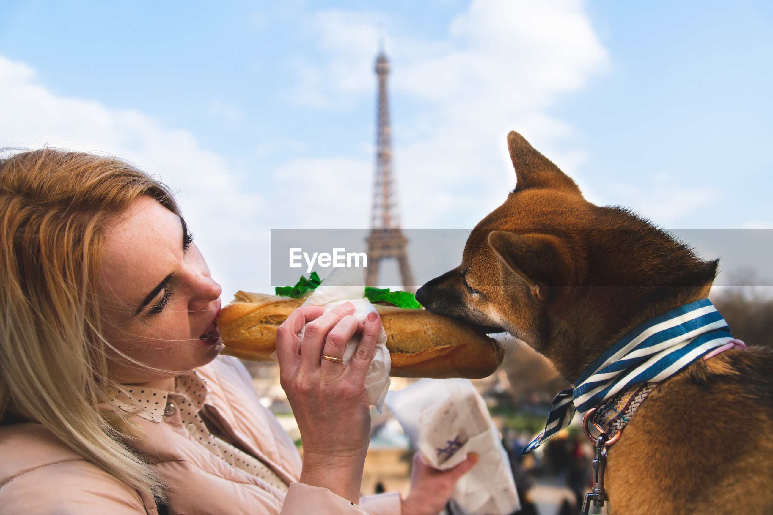 Woman with dog eating bread against eiffel tower