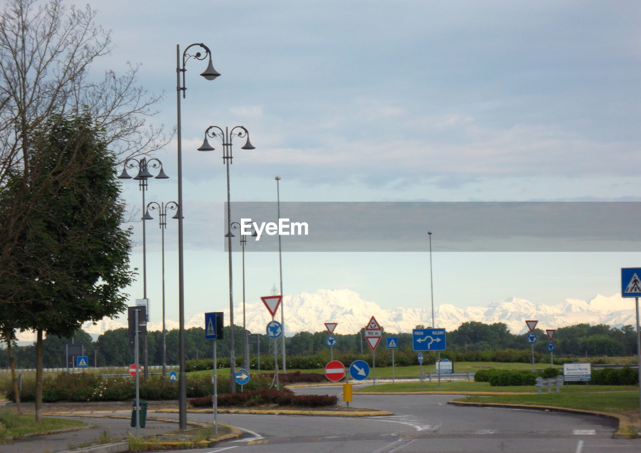 sky, street light, transportation, cloud - sky, road, day, tree, street, car, outdoors, no people, road sign, architecture, city, nature