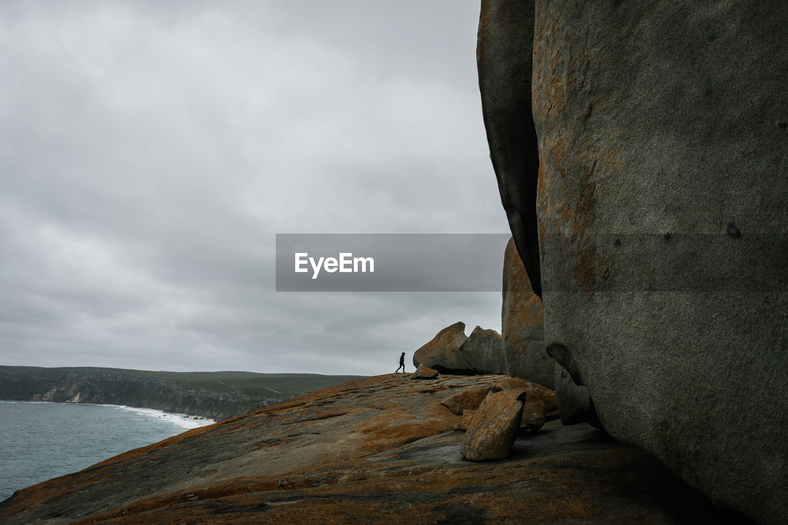 Low angle view of woman on rock formation against sky