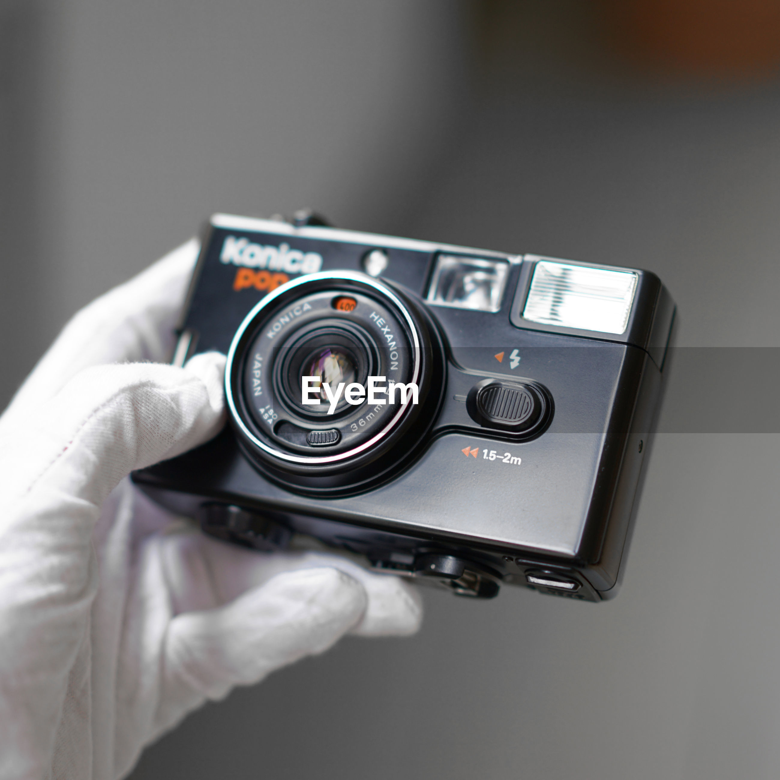 CLOSE-UP OF HAND HOLDING CAMERA WITH MOBILE PHONE