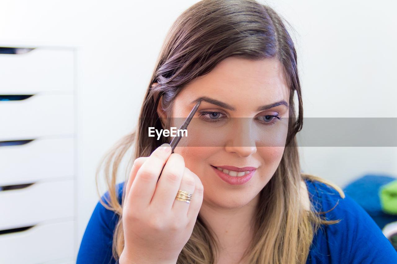 Close-up of young woman applying make-up at home