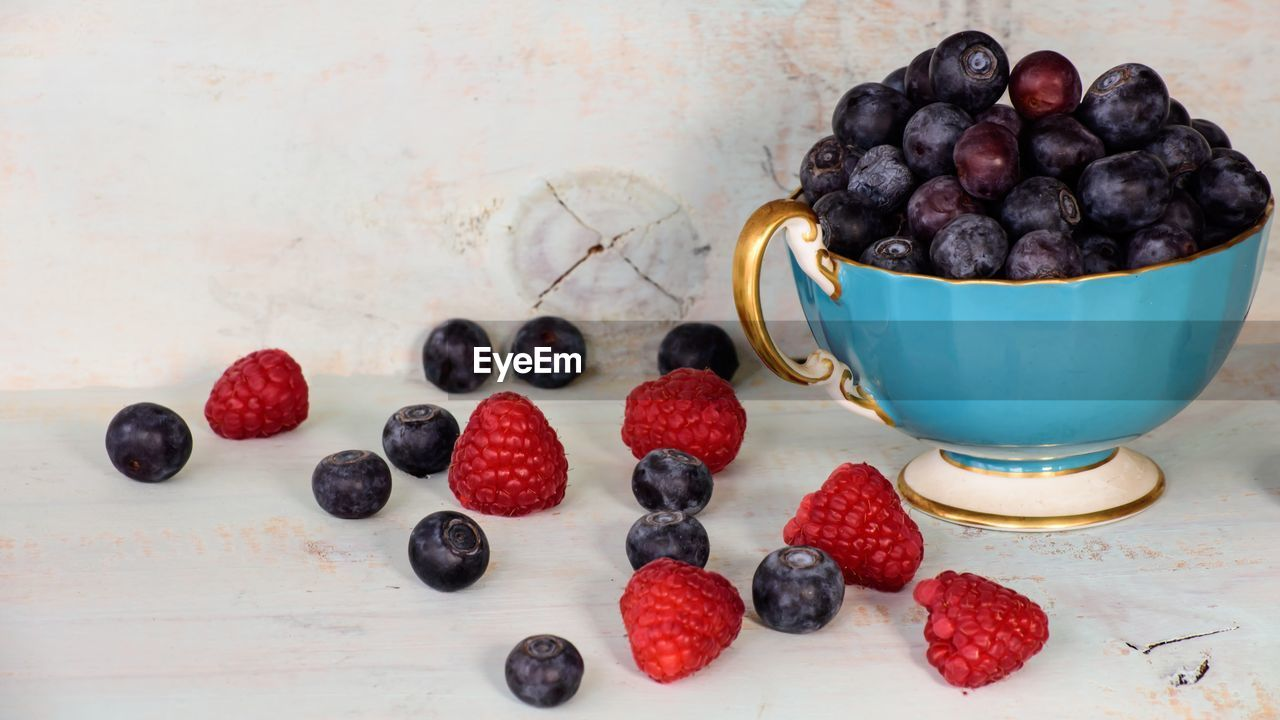 berry fruit, food, food and drink, fruit, healthy eating, freshness, blueberry, wellbeing, indoors, table, still life, no people, bowl, kitchen utensil, large group of objects, close-up, high angle view, raspberry, eating utensil, spoon