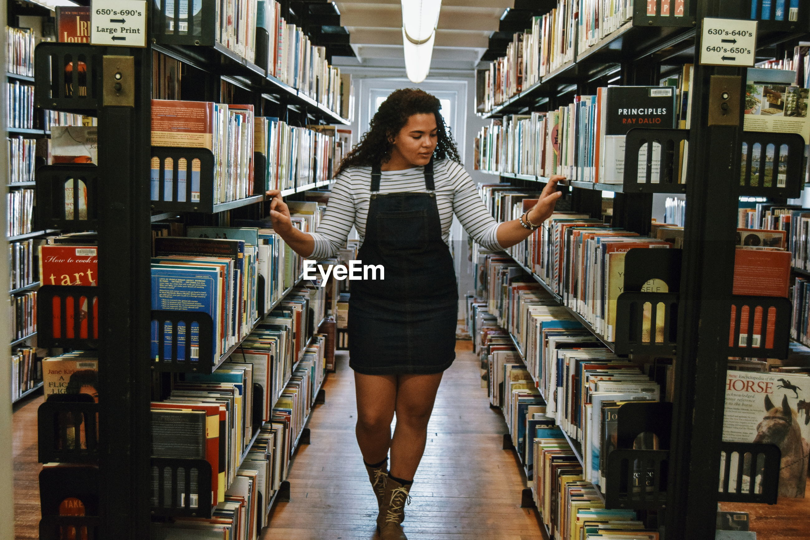 FULL LENGTH OF YOUNG WOMAN STANDING IN LIBRARY