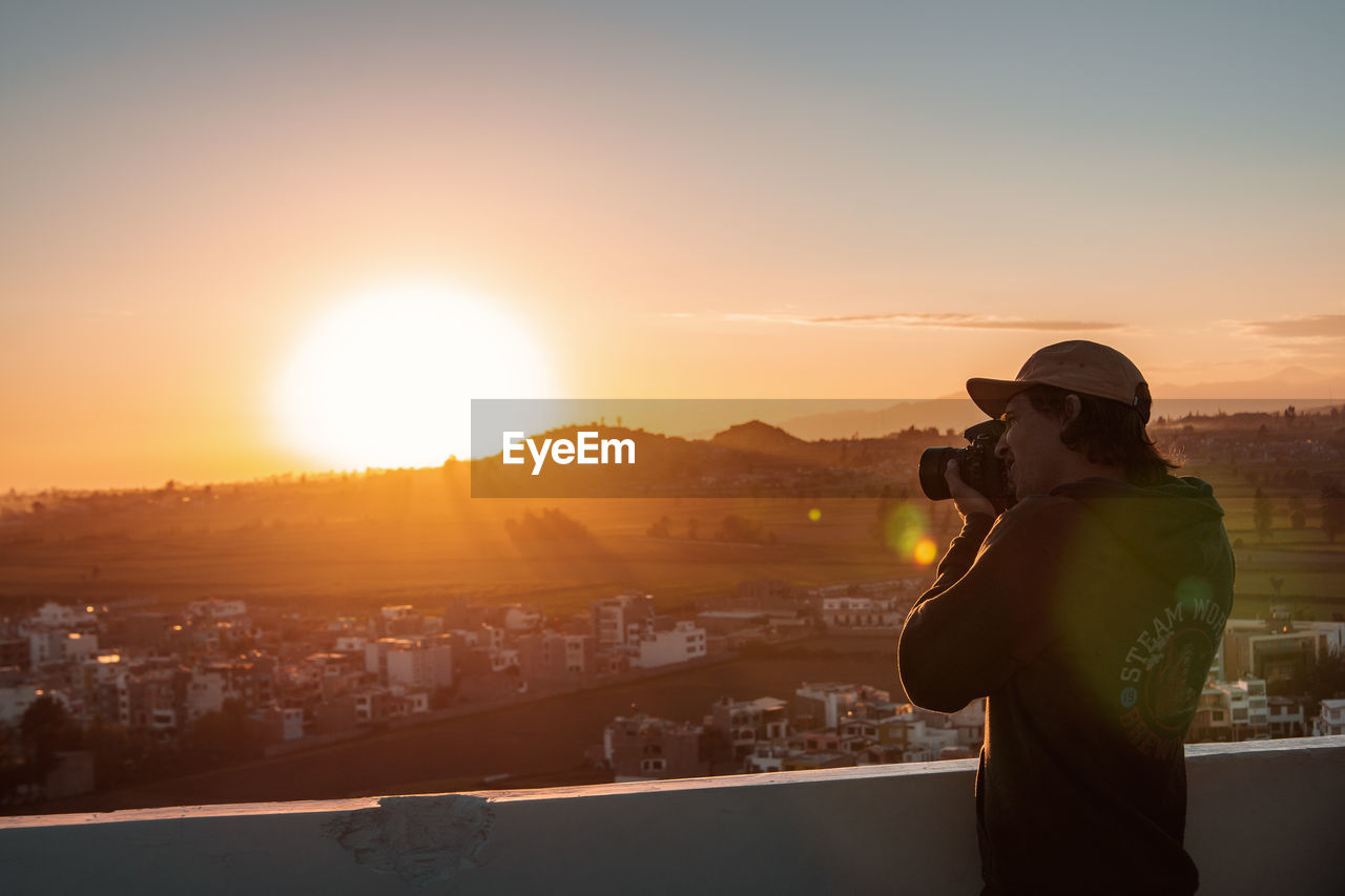 sunset, sky, real people, one person, sunlight, architecture, building exterior, cityscape, nature, orange color, built structure, city, sun, lifestyles, mountain, lens flare, leisure activity, standing, photography themes, outdoors, photographer