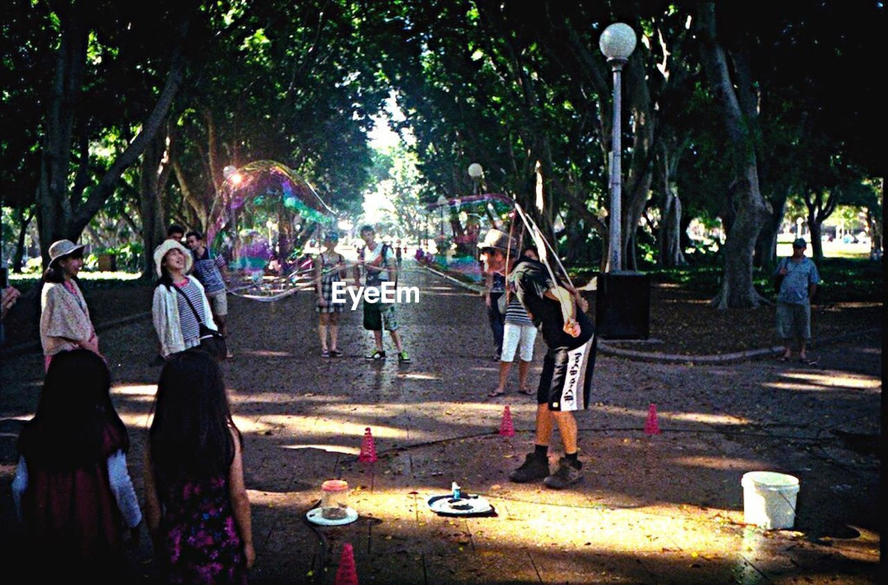 tree, real people, outdoors, fun, enjoyment, leisure activity, night, standing, lifestyles, togetherness, men, full length, party - social event, women, friendship, bubble wand, city, people, adult