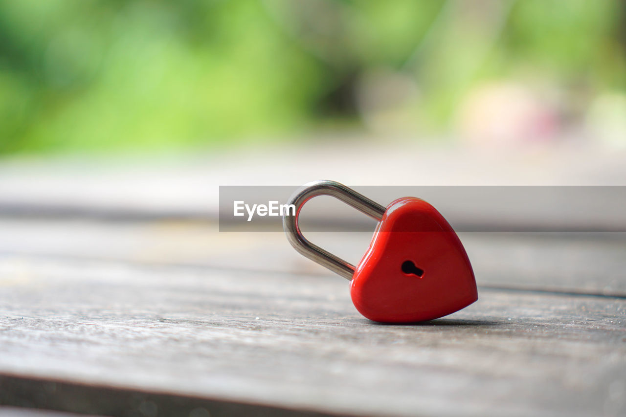 selective focus, red, no people, close-up, metal, still life, day, single object, focus on foreground, wood - material, outdoors, representation, positive emotion, love, nature, table, green color, heart shape, toy
