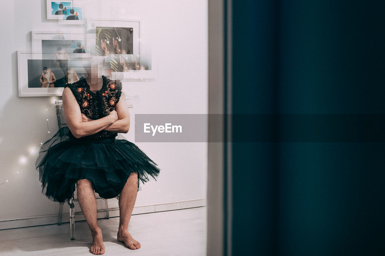 Digital Composite Image Of Man Wearing Dress With Frames By Wall