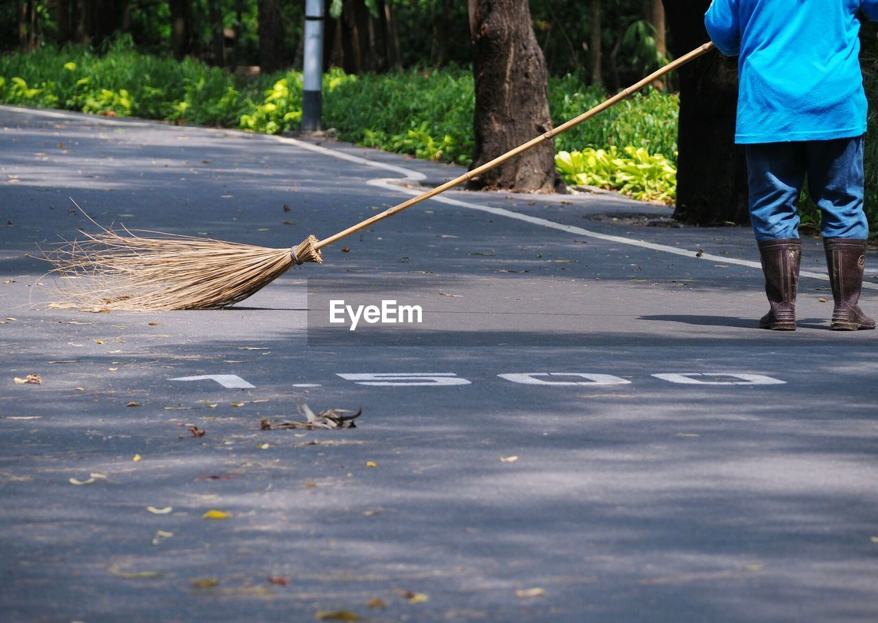real people, one person, day, low section, road, nature, men, street, city, lifestyles, transportation, outdoors, human leg, casual clothing, footpath, holding, motion, human body part, broom, walking cane